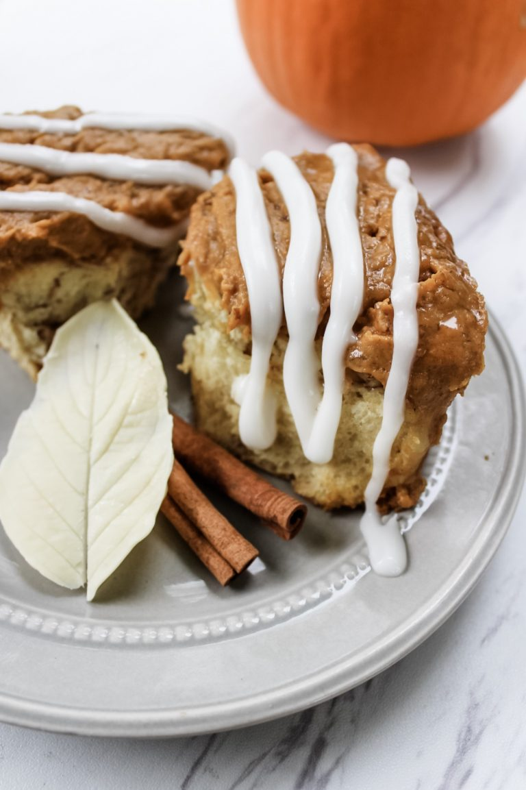Up close shot of cinnamon roll pumpkin pudding pie. There is a pumpkin out of focus in the top right corner. The two pieces of pie are on a grey plate and drizzled with icing. The plate is also decorated with cinnamon sticks and a decorative white chocolate leaf.
